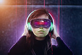 Young female in virtual reality goggles and headphones. Face recognition system concept.