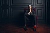 Portrait of sitting businessman in strict gray suit and colorful multi colored socks. Business and success concept.