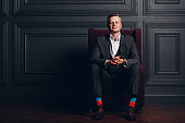 Portrait of  businessman in strict gray suit and colorful multi colored socks. Business and success concept.