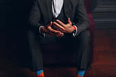 Businessman in strict gray suit and colorful multi colored socks. Business and success concept.