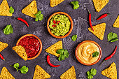 Mexican food background: guacamole, salsa, cheesy sauces with ingredients on black background