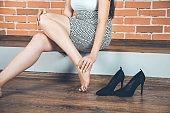 fashion woman ache feet on brick wall background