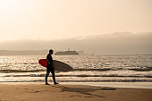 Surfer walking with surfboard on the seashore beach at sunset or sunrise. Silhouette of surf man looking for the high waves. Outdoors water sports, vacation and adventure lifestyle concept.