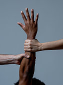 Black African American and Caucasian hands holding together. White and black skin arms in world united against racism, racial love and understanding races diversity and Human rights cooperation concept