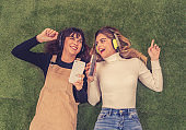 Two gorgeous and cheerful teen girl friends listening online music on mobile smart phone having fun singing lying on grass . Positive emotions, friendship, people, leisure and technology concept.