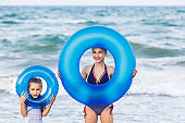 happy girls hold floating inflatable circles on sea beach.