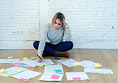 Worried young woman feeling stressed and desperate on the ground with calculator accounting expenses not able to pay mortgage. In paying debts and domestic bills and financial problems.