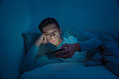 Young mobile phone addict man awake at night in bed using smartphone for chatting, flirting and sending text message. In communication, Internet addiction and Social media network abuse concept