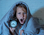 Cute sleepless little girl lying in bed showing alarm clock looking tired having sleeping troubles staying asleep at night or waking too early in Children Insomnia Anxiety and Sleep Disorders.