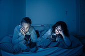 Life style portrait of young bored couple in bed at night on smart phones obsessed with games, social media, apps ignoring each other. Relationship communication problems and phone addiction concept.