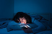 Addicted young woman chatting and surfing on the internet using her smart phone sleepy, bored and tired late at night. Dramatic dark light. In Internet, Mobile addiction and insomnia concept.