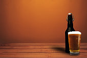 Glass of beer and black bottle beer on a red wood table wood. Beautiful  orange wall background.