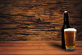 Glass of beer on a old oak table of wood. Beautiful brown wooden background.