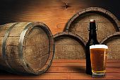 Wooden barrel background and glass of beer on a old oak table of wood.