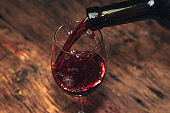 Pouring Red wine bottle and glass of wine  on a old wooden table.