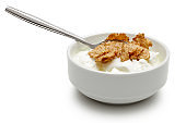 Cereal and yoghurt in bowl isolated on white