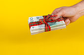 A hand holding a bundle of Polish banknotes wrapped in a bow as a financial prize on a yellow background