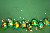 Easter eggs, dark green with gold on a green background. View from above. Flat lay.