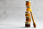Five Small glass jar with metal cap with different kinds and colours of honey one on another and spoon isolate and on grey cement background with copy space. Healthy product, natural. Horizontal