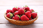 Strawberries in the basket on grey wooden background