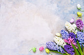 Easter background. Hyacinth flowers bouquet and decorative Easter eggs. Copy space, top view.
