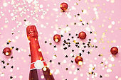 Champagne bottle with Christmas decoration on pink background. Top view, copy space