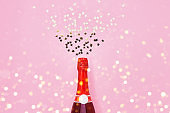 Red Champagne bottle with confetti stars on pink background. Top view, copy space