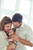Loving parents holding their infant daughter at home