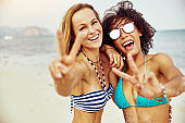 Two smiling women giving the peace sign on a beach