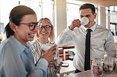 Young businesspeople laughing together during their office coffee break