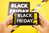 Close-up of unrecognizable woman using smartphone and posting Black Friday advertisement on social media