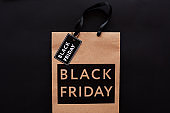 Close-up of shopping paper bag with tag in black color, Black Friday advertisement