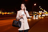 Cheerful attractive business lady in long jacket chatting by cell phone while waiting for taxi at road