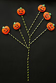 Tree-shaped creative composition of Halloween sweets in shape of pumpkins on straws placed on dark background