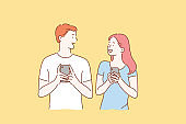 Concept of a young couple in love excited man and woman smiling. Boy and Girl meet or talk, both using mobile phones