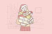 Positive, successful, emotional Santa girl concept. Young, happy woman or teenager in a Santa hat keeps boxes of gifts at home for Christmas or New year