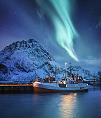 Aurora Borealis, Lofoten islands, Norway. Nothen light, mountains and boat. Winter landscape at the night time. Norway travel - image