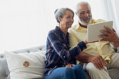 Couple sitting on couch while using a tablet