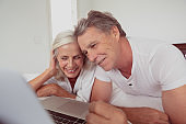 Active senior couple using laptop while lying on bed in bedroom at comfortable home