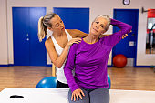 Female physiotherapist giving arm massage to active senior woman in sports center