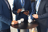 Business people discussing over digital tablet while having coffee in office