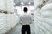 Thoughtful male supervisor standing in warehouse