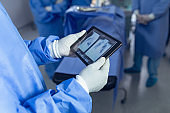 Surgeon looking x-ray report on digital tablet in operating room at hospital