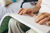 Senior male patient is reading in a retirement home
