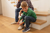 Son tying his father shoelaces in a comfortable home