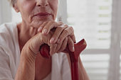 Active senior woman leaning on walking cane in a comfortable home