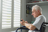 Active senior man in wheelchair using mobile phone at home