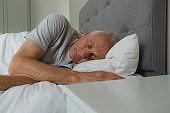 Active senior man sleeping in bed in bedroom