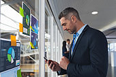 Businessman using mobile phone near glass wall in office