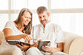 Mature couple on a couch with tablet